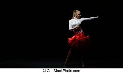 Girl dancing cha-cha-cha in a studio on a dark background -...