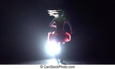 Girl dancing cha-cha-cha on a dark background with light illuminator. Slow motion