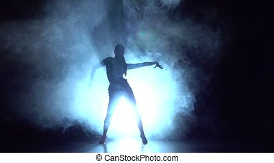 Girl dancing elements of sport - ballroom dance in the studio, silhouette. Slow motion