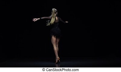Girl dancing ha-cha-cha in the studio, black background. Slow motion