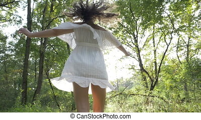 Girl dancing happily in the woods dressed in a angelic white dress