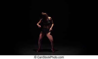 Girl dancing hip-hop movement in dark studio. Slow motion