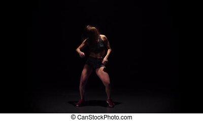 Girl dancing hip-hop movement in dark studio. Slow motion
