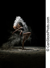 Girl dancing in a cloud of white dust studio portrait