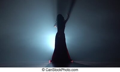 Girl dancing in dress on black smoke background. Sihouette. Slow motion