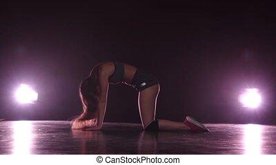 Girl dancing in short shorts. Studio