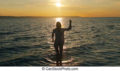 girl dancing in the sea in the sunset