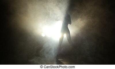 Girl dancing in the studio in the smoke