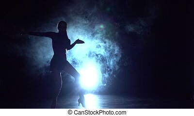 Girl dancing latin dance in the studio, silhouette. Slow motion