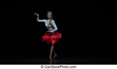 Girl dancing latin, dark background. Slow motion