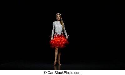 Girl dancing latin in a studio on a dark background