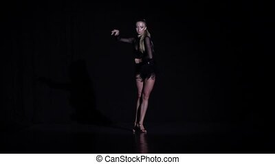 Girl dancing latina in the studio, black background. Slow motion