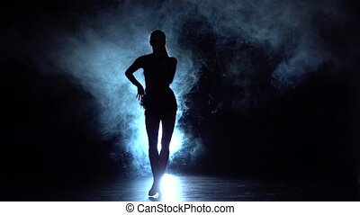 Girl dancing movements of salsa, rumba. background illuminated. Slow motion
