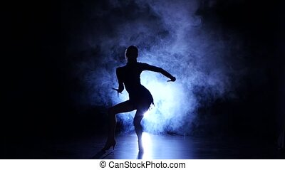 Girl dancing movements of salsa, rumba, silhouette. Dark background, blue backlight