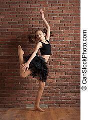 Girl dancing near brick wall