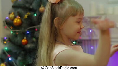 Girl dancing on the background of the Christmas tree