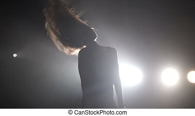 Girl dancing on the background of the spotlight. Silhouette