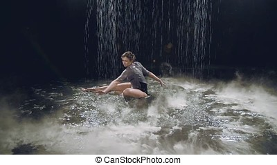 girl dancing on the water in the studio on a black background