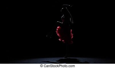 Girl dancing passionate latin dance, silhouette. Slow motion