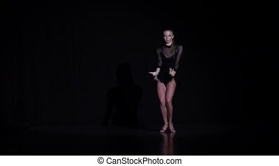 Girl dancing rumba elements in the studio, black background. Slow motion