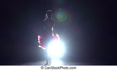Girl dancing rumba on a dark background with light...