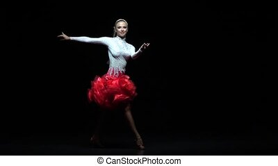 Girl dancing salsa, dark background. Slow motion