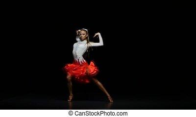 Girl dancing samba in a studio on a dark background