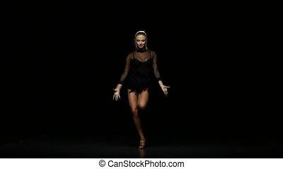 Girl dancing samba in a studio on a dark background -...