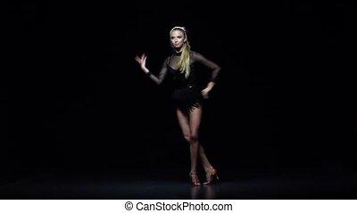 Girl dancing samba in the studio, black background. Slow motion