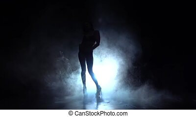 Girl dancing sexy dance in high heels. Black smoke background. Silhouette. Slow motion