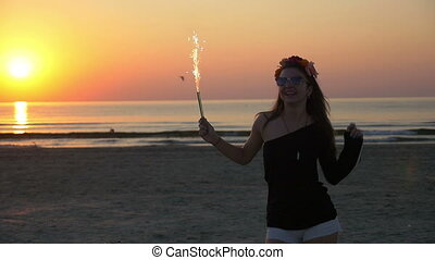 Girl dancing with a firework candle at twilight on a sandy beach at sunset
