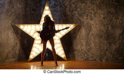 girl dancing with electric guitar, shining star in the background. slow motion, silhouette