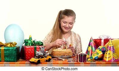 Girl decorates a cake with candles, sitting at the table. Gifts scattered around her