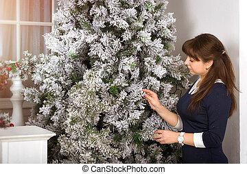 Girl decorates a Christmas tree