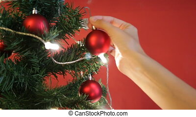 Girl decorates a Christmas tree with red toys on red background