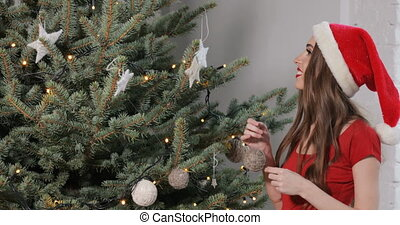 Girl Decorates Christmas Tree - Excited caucasian girl...
