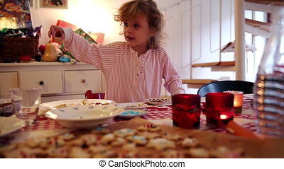 Girl decorates cookies on advent first - A little girl puts...