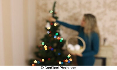 girl decorates the Christmas tree in the defocusing at home