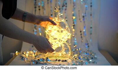 Girl decorating a garland background, Christmas background shimmering with lights