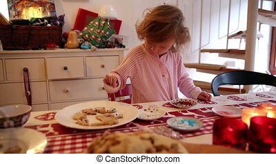 Girl decorating cookies with her mother on advent first