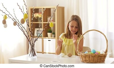 girl decorating willow by easter eggs at home - easter,...