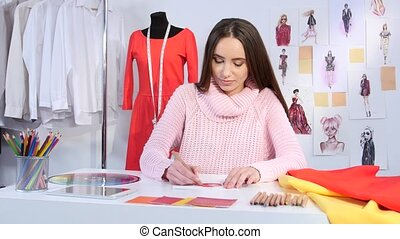 Girl designer draws a sketch of red dress for a youth fashion magazine