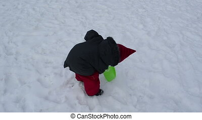 girl dig snow frozen - girl tries to dig the frozen snow in...