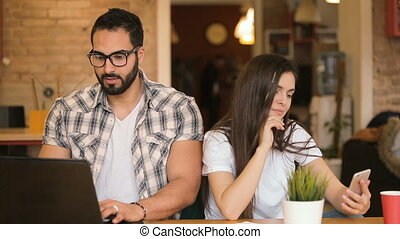 Beautiful girl distracting busy boy with selfie, busy man in checked shirt typing on the laptop, smiling woman with black long hair taking selfie with smartphone, indoor shot in european educational cafe