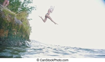 Girl dives into the water from a rock in nature, slow motion