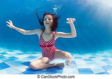 Girl diving underwater in swimming pool