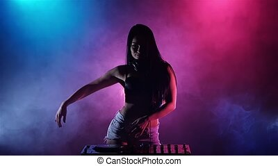 Girl DJ dancing develop her hair behind her multicolored lights and smoke. Slow motion