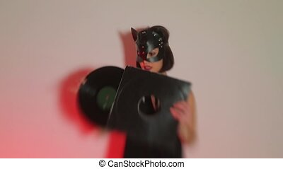 Girl DJ in a cat mask holds in her hands a vinyl record at a kinky party.