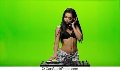 Girl DJ turntables and sexy twist erotic dancing, her hair is developing in different directions. Green screen. Slow motion
