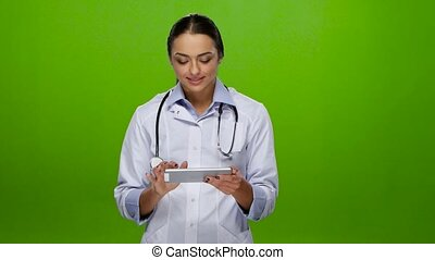 Girl doctor smiling working on the tablet pc